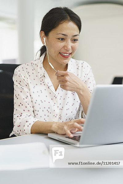 Lächelnde Geschäftsfrau mit Kopfhörer bei der Arbeit am Laptop am Bürotisch