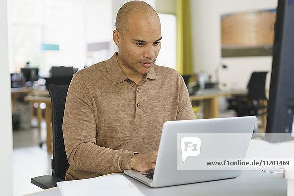 Seriöser Geschäftsmann mit Laptop im Kreativbüro