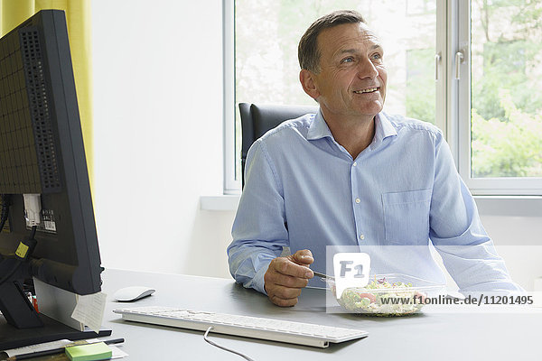 Smiling businessman having salad while sitting at desk in creative office