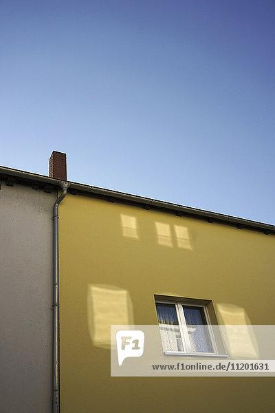 Flachwinkelansicht des gelben Wohngebäudes gegen den klaren blauen Himmel