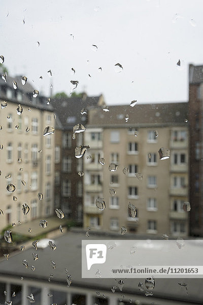 Gebäude gegen den Himmel durch nasses Glasfenster gesehen