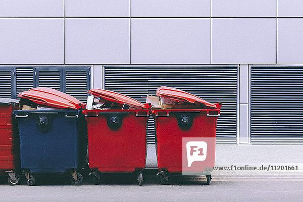 Rote und blaue Mülltonnen am Straßenrand an der Wand