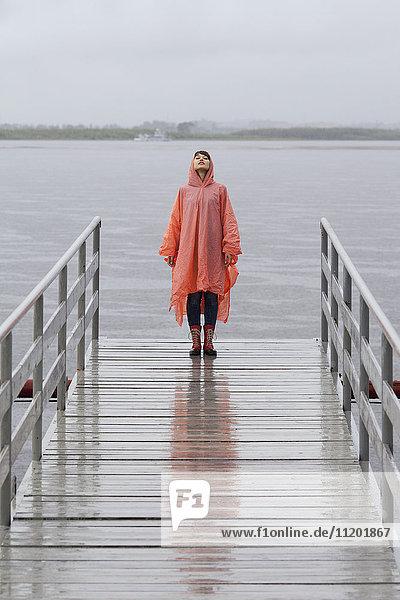 Frau im Regenmantel am Steg während der Regenzeit