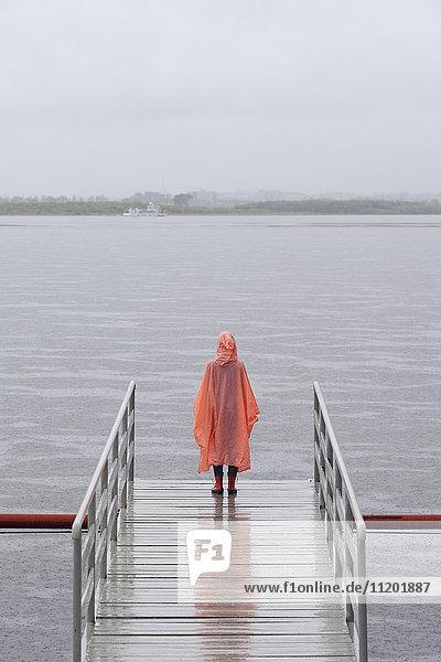Rückansicht der Frau im Regenmantel am Steg gegen den klaren Himmel