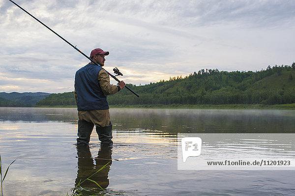 Mann hält Angelrute  während er im Fluss gegen den Himmel steht.