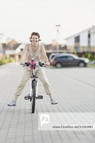 Porträt einer glücklichen Frau beim Radfahren auf der Kopfsteinpflasterstraße