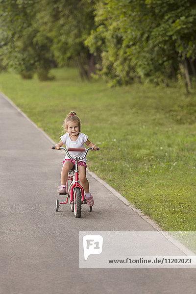 Lächelndes süßes Mädchen  das auf der Straße durch das Grasfeld im Park radelt.
