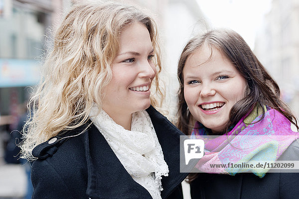 Two female friends smiling outdoors