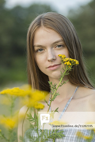 Porträt einer schönen Frau mit gelben Blumen im Park
