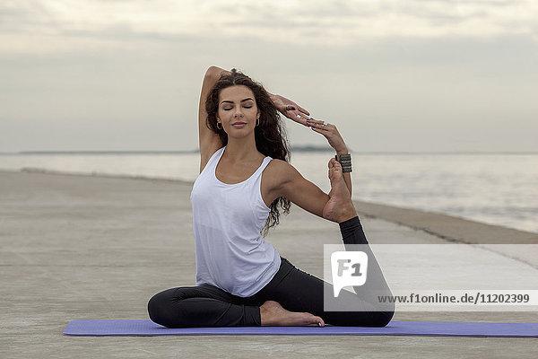 Beautiful woman practicing yoga in mermaid pose at beach