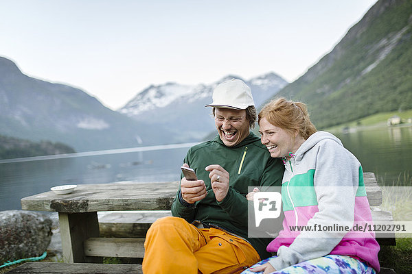 Laughing couple at lake looking at cell phone