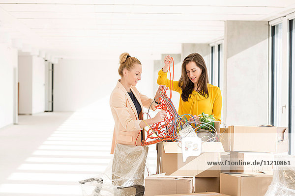 Young businesswomen untangling cords while standing by cardboard boxes in new office
