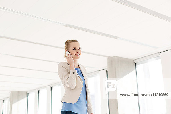 Smiling young businesswoman using mobile phone in new office