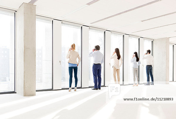 Full length rear view of business people using mobile phone in new office