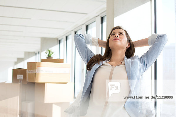 Thoughtful young businesswoman with hands behind head in new office