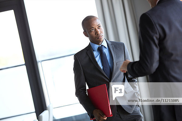 Young businessman holding file while listening to male colleague in office