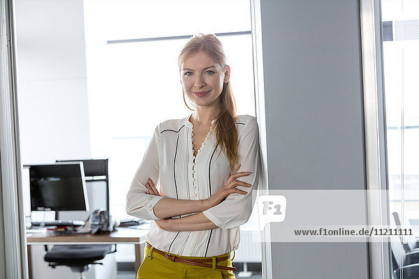 Portrait of smiling young businesswoman with arms crossed in doorway of office
