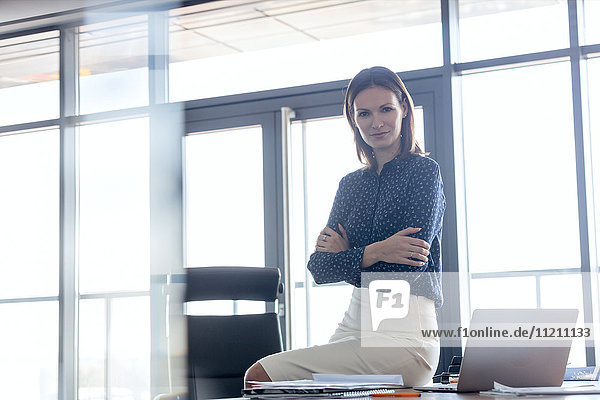 Portrait of young businesswoman sitting arms crossed on desk in office