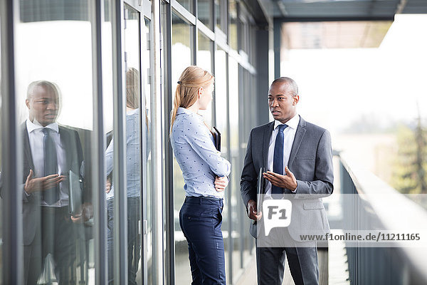 Businessman discussing with female colleague on office balcony