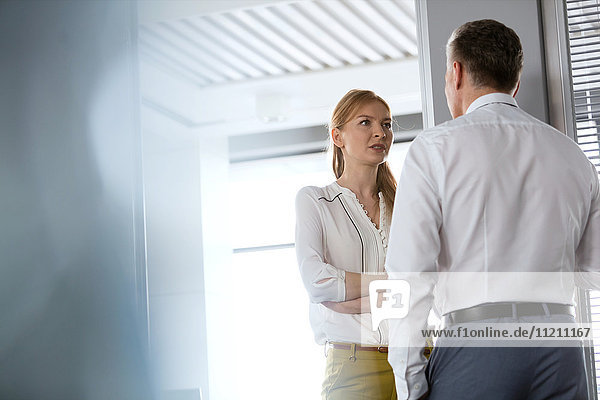 Young businesswoman talking with male colleague in office