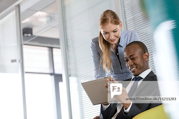 Smiling young businesswoman with male colleague using digital tablet in office