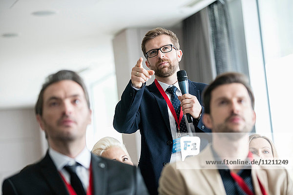 Businessman gesturing while asking question during seminar