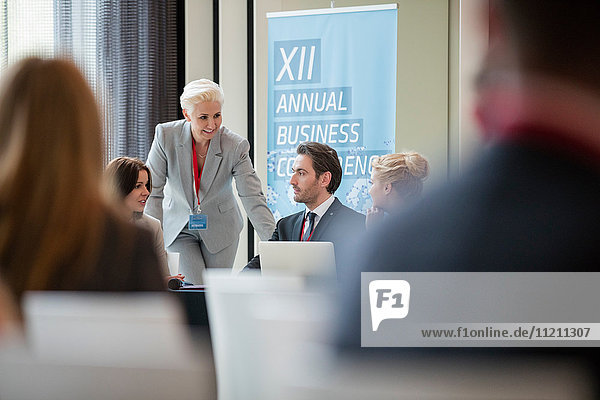 Businesswoman talking to colleagues during seminar