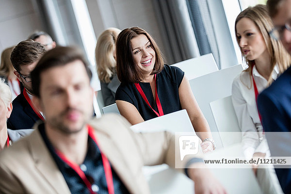 Happy businesswoman sitting with colleagues in seminar hall