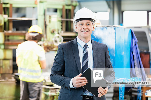 Portrait of confident mature businessman holding digital tablet with worker in background at factory