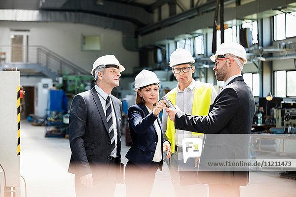 Team of business people examining machine part in metal industry
