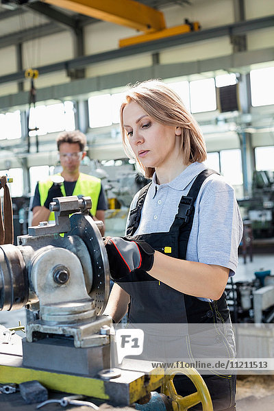 Mature female worker working on machinery with colleague in background at factory
