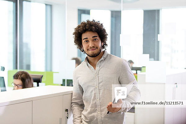 Portrait of young businessman holding laptop in office