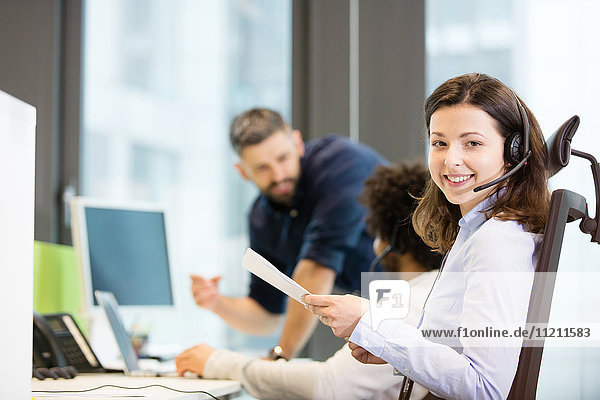 Portrait of smiling customer service representative holding documents with colleagues in background at office