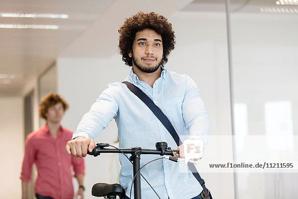 Young businessman holding bicycle with colleague in background at office