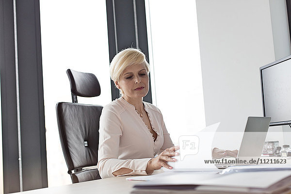 Mature businesswoman reading document at desk in office