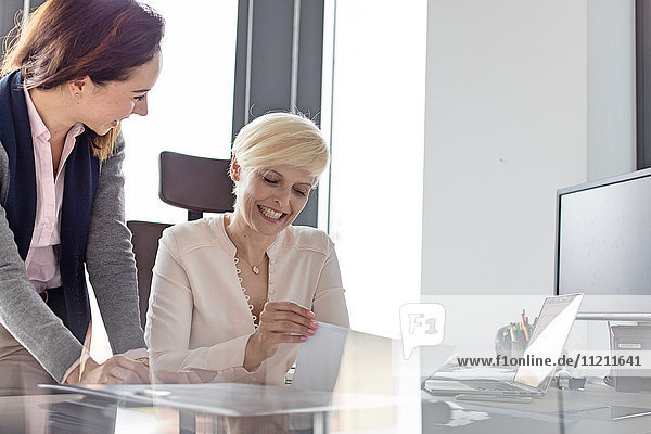 Smiling businesswoman and female manager with project in office