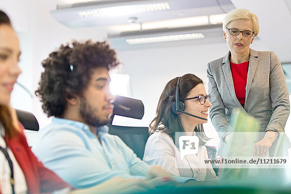 Mature businesswoman with operators working in office