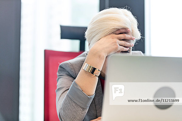 Tired mature businesswoman with head in hands at office
