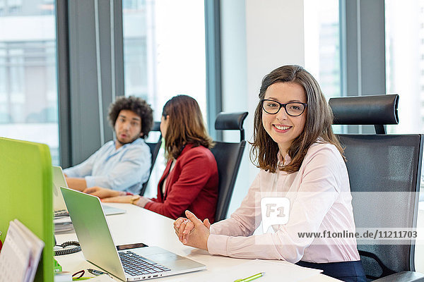 Portrait of smiling young businesswoman with laptop while colleagues in background at office