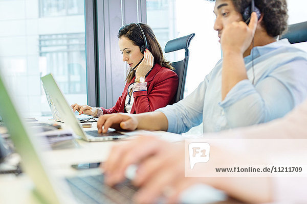 Young businesswoman using headset and laptop with colleagues in foreground at office