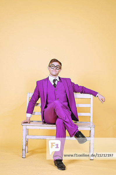Man in Purple suit sitting on park bench