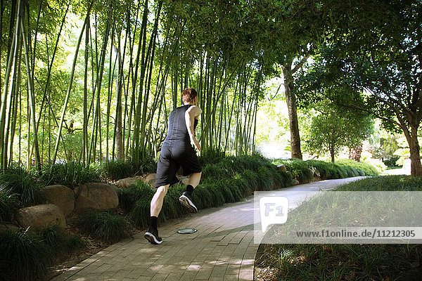 Rear view of man running in park