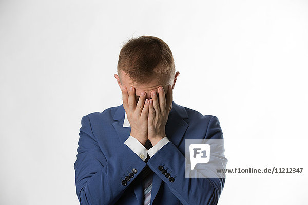 depressed businessman with holding his head in hands