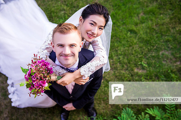 High angle portrait of happy wedding couple standing on grassy field