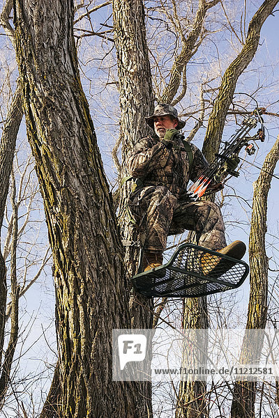 Bowhunter In Tree Stand in Winter