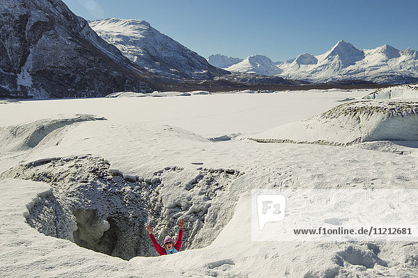 A woman makes her way to the top of Valdez Glacier through a ice cave opening  Southcentral Alaska  winter
