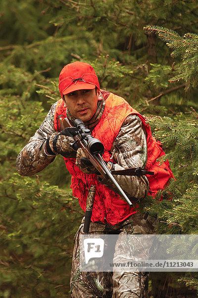 Whitetail Deer Hunter In Blaze Orange Takes Aim With Rifle