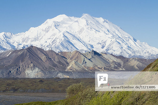 Pair of bikers on the park road with Denali in the background  Denali National Park & Preserve  Interior Alaska  USA