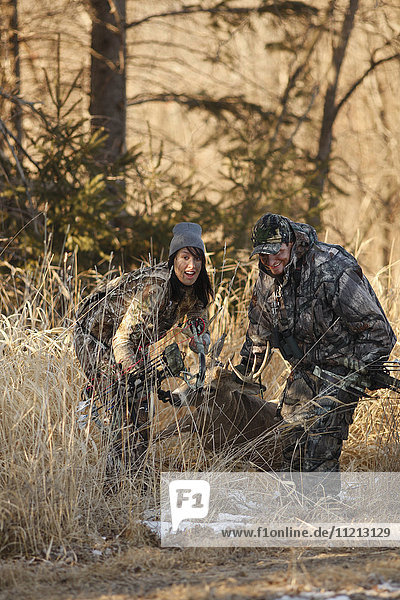 Hunters Dragging Whitetail Buck Out Of Woods