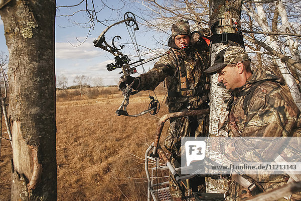 Father Coaches Son On Bowhunting In Deerstand
